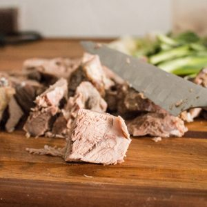 Cutting cooked lamb shoulder into chunks