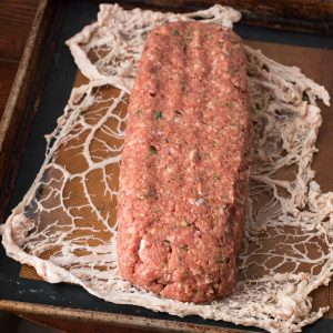 Wrapping lamb and goat bacon meatloaf in caul fat