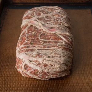 Lamb and goat bacon meat loaf formed and wrapped in , caul fat