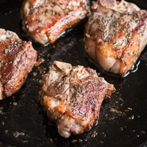 Searing rosemary lamb chops in a pan