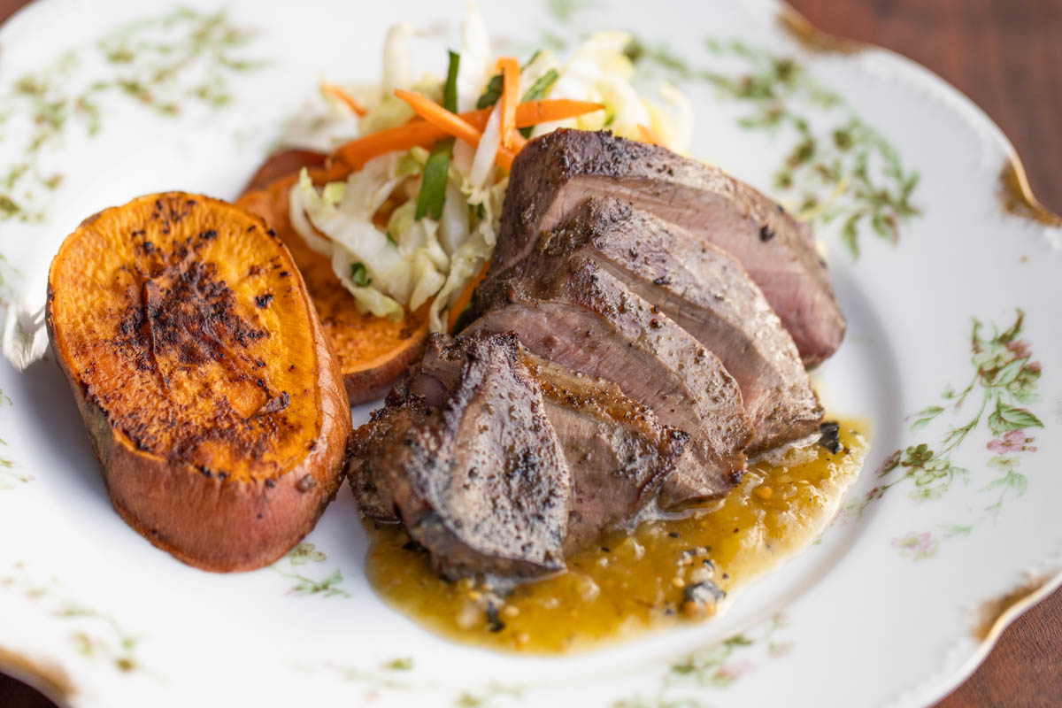 sliced grilled lamb heart with salsa verde sweet potatoes and cabbage slaw