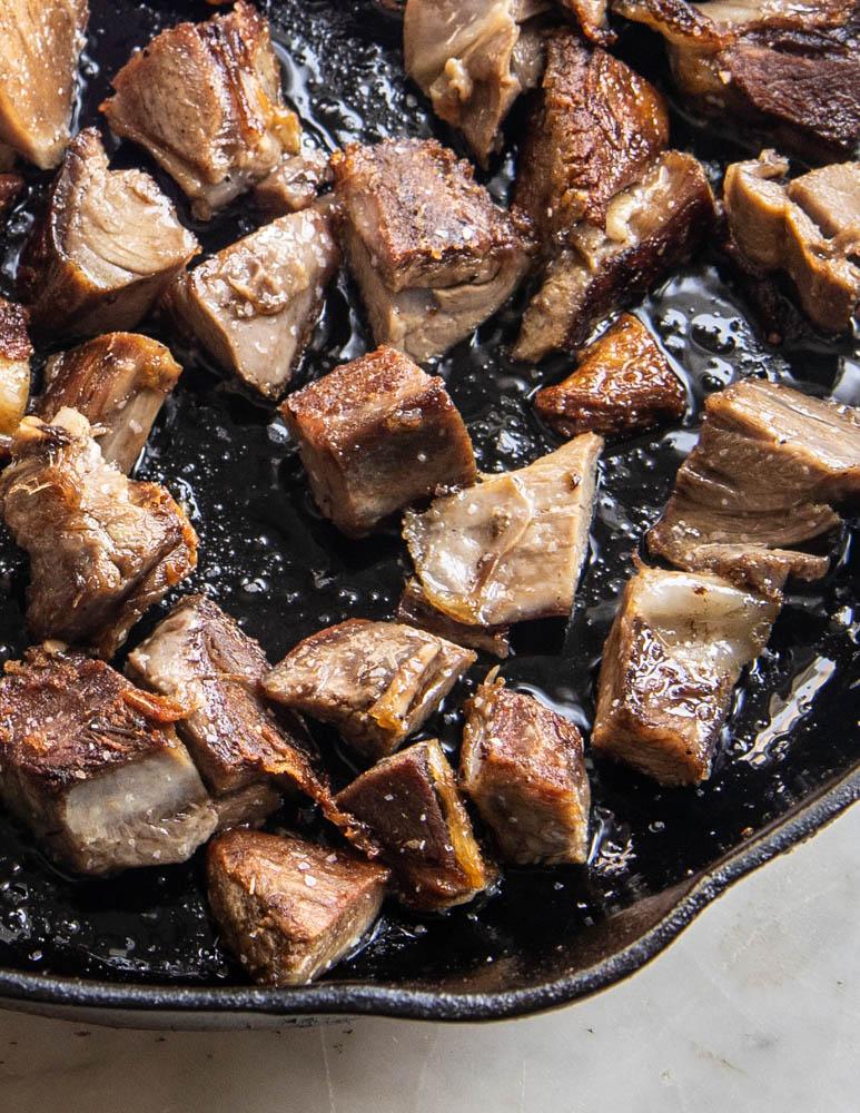 Frying goat shank meat in a pan